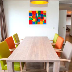 Hier zie je een van onze locaties. Op de foto is een tafel met stoelen en een schilderij te zien.